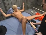 Naughty blonde gets machine fucked in the jail cell.