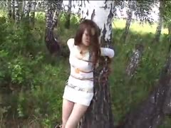 Helpless bound to a tree in forest