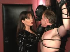 Sadistic Lady Ramirez in leathers ties a man in a dungeon cross