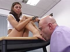 Dominating a bald man with her boots and feet