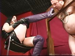 Evil dominatrix with her restrained slave