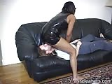 Busty black girl in black latex dress riding a white man's face